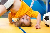 stock photo of upside  - baby standing upside down on gym mat - JPG