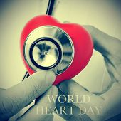 pic of auscultation  - closeup of a doctor auscultating a red heart with a stethoscope and the text world heart day - JPG