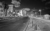 foto of israel people  - Wide angle black and white long exposure view of the Tel Aviv Israel beach promenade at night with blurred people and riders - JPG