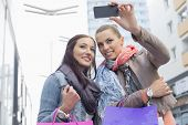 image of two women taking cell phone  - Female friends with shopping bags taking photos through mobile phone - JPG