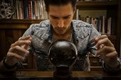 image of clairvoyance  - Handsome young man predicting the future by looking into black crystal ball