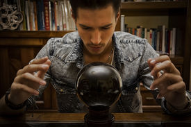 foto of occult  - Handsome young man predicting the future by looking into black crystal ball  - JPG