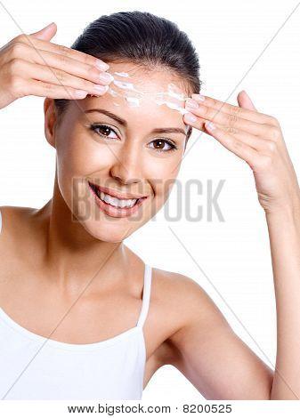 Happy Woman Applying Cream On Her Forehead