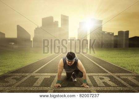 Fat Person Kneeling On Running Track
