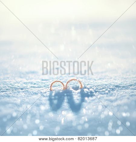 Wedding Concept - Two Gold Rings On The Snow In Winter Day