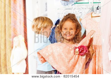 Laughing girl holds dress, boy behind her in shop