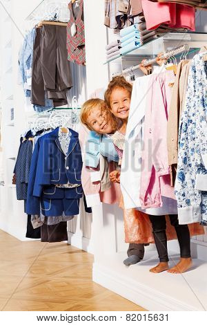 Happy boy and girl play hide-and-seek in clothes