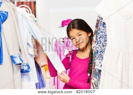 Small Asian girl in shop holds arm of white shirt