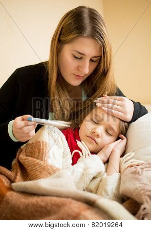 Young Mother Embracing Sick Daughter And Checking Thermometer