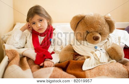 Sad Girl Measuring Temperature With Teddy Bear In Bed