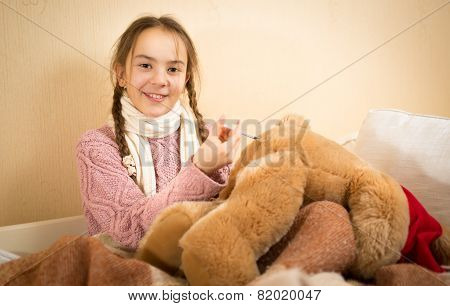 Little Girl Playing In Doctor And Doing Injection To Teddy Bear
