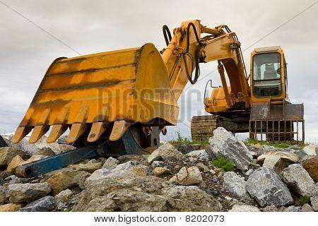Excavator On  Heap Of Stones
