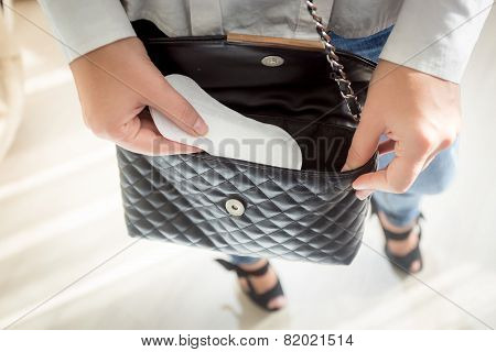 Young Woman Putting Menstrual Pad Out Of Handbag
