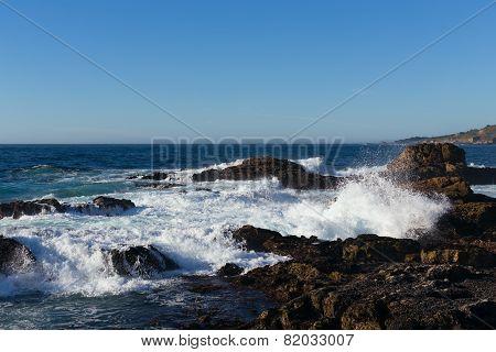 Ocean waves breaking on shoreline rocks