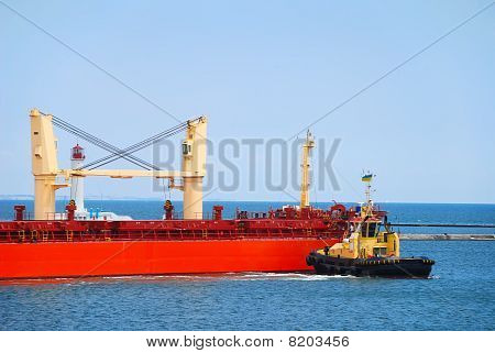 Tug Boat Helps To Maneuver The Ship