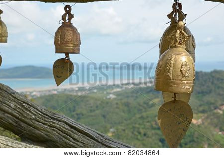 Phuket, Thailand-Sept,23 2014:Buddhist bells on the background of the top view of the coast of Phuke