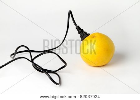 Black electric cable stab in fresh yellow grapefruit