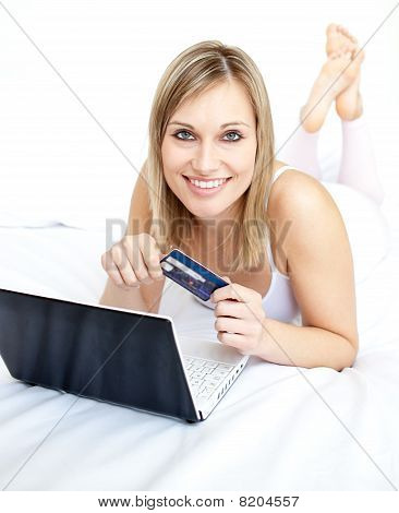 Radiant Woman Lying With A Laptop On Sofa