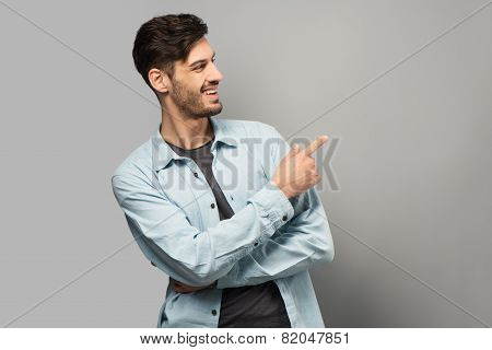 Smiling young man pointing at something