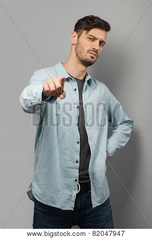 Thoughtful young man pointing at camera