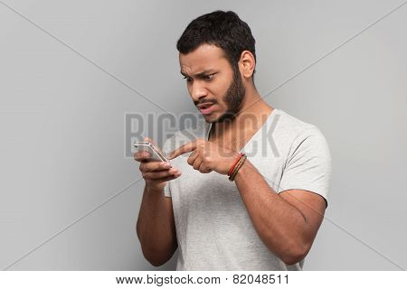 Photo of young mixed race man using phone