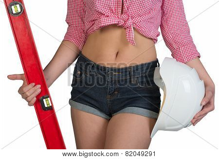Woman holding builders level and hard hat