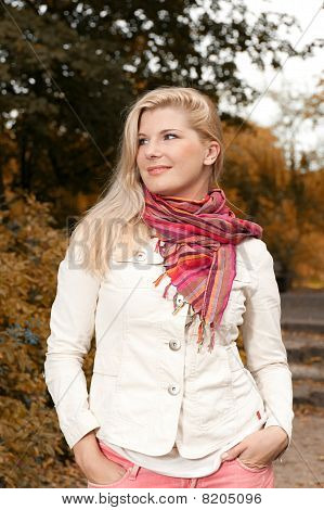 beautiful autumn woman standing in yelllow park