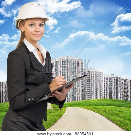 Businesswoman in hard hat, writing on clipboard