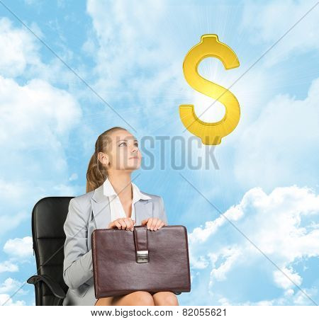 Businesswoman sitting on office chair, looking up at dollar sign in the air