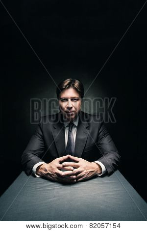 Man wearing suit in dark room illuminated by light