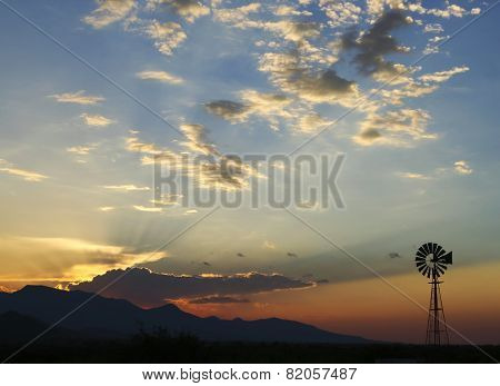 A Lone Windmill Stands Silhouetted At Sunset