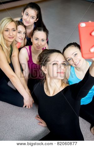 Group Of Beautiful Sporty Girls Posing For Selfie, Self-portrait With Smart Phone In Sports Gym