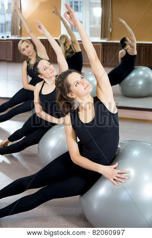 Group Of Young Women Practice On Pilates Fitballs