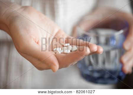 Womans Hands Holding Heap Of White Round Pills And Glass Of Water