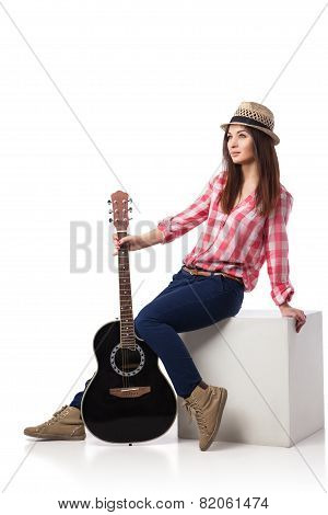 young woman musician with guitar sitting on cube
