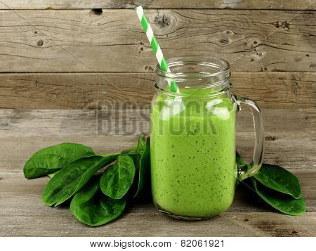 Green smoothie with spinach on wood