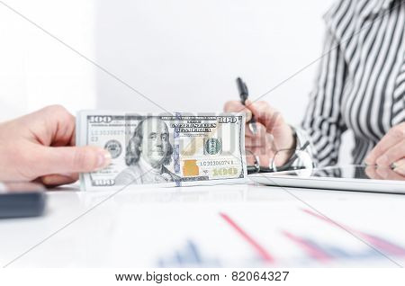 Business people exchanging dollar banknotes