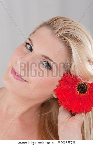 Beautiful woman with pure healthy skin holding big herber flower
