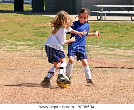 Two Young Girls Fighting For The Soccer Ball
