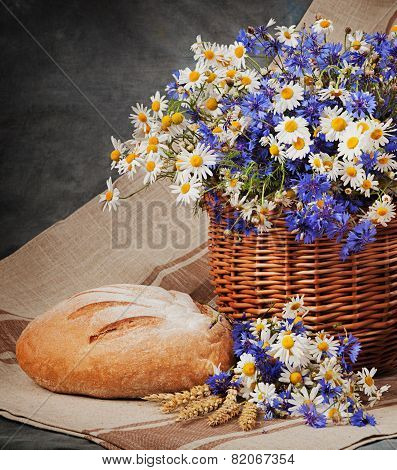 Still Daisies And Cornflowers In The Basket. Bread And Milk On The Table