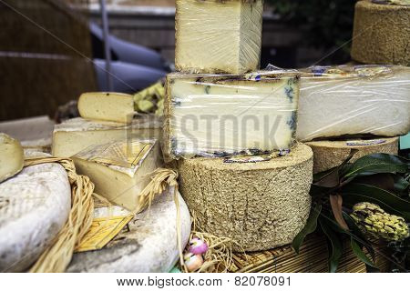 Cheese and sausages exposure in a market stall. Color image