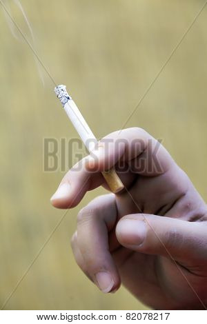 Cigarette in hand close up. Color image