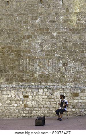 San Gimignano, Tuscany, street musician. Color image