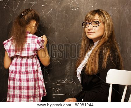 teacher with pupil in classroom at blackboard writting