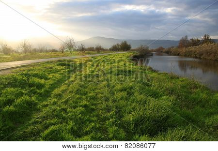 Green Field And River Lit By Strong Sun Light