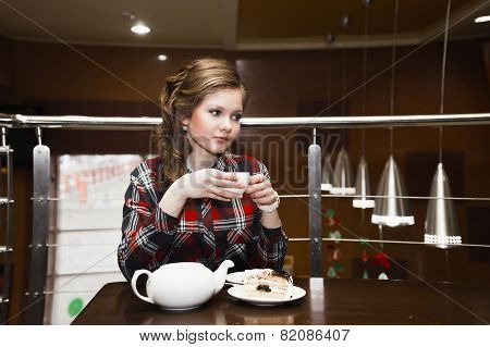 Young Women In A Plaid Shirt Drinking Tea In A Cafe