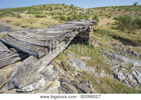 Top of bridge with wood beams and stones, dried up stream