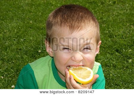 The child winced bites sour lemon