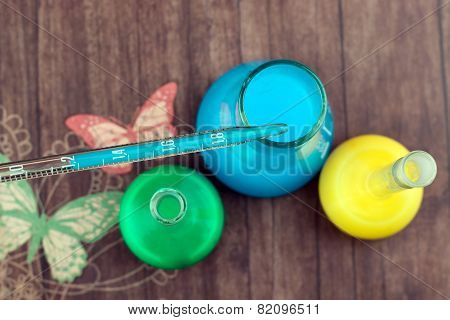 Pipette And Colored Bulbs On A Table