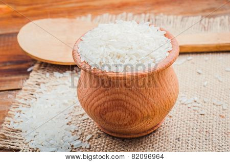 rice in a pot and spoon on burlap